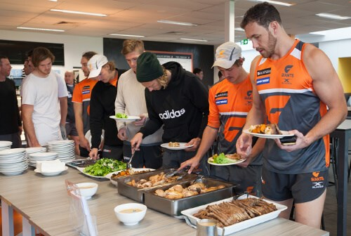 athletes taking servings of buffet food