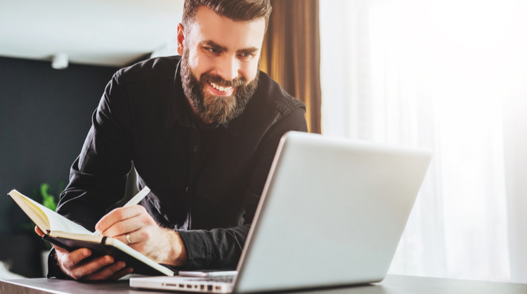 bearded man smiling and reading something on laptop