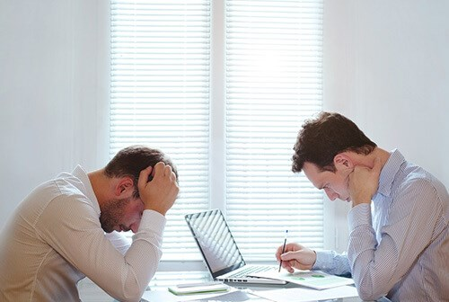 male colleagues looking down and frowning at work