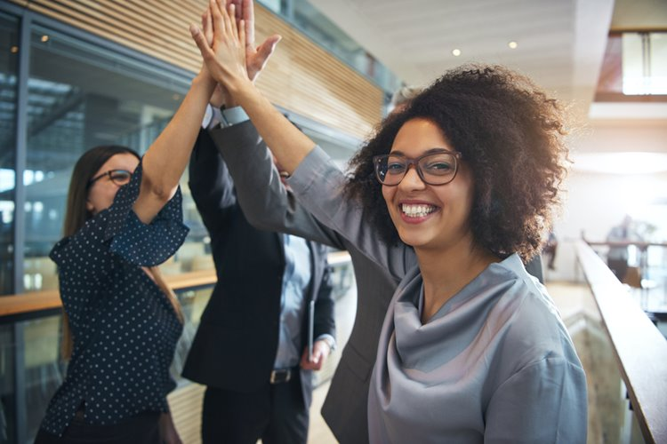 dark-skinned woman with curly hair high fiving colleagues