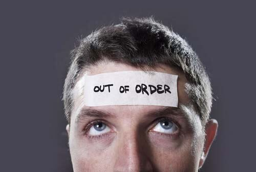 man with 'out of order' sign taped to forehead
