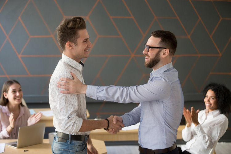 male team leader giving man employee handshake