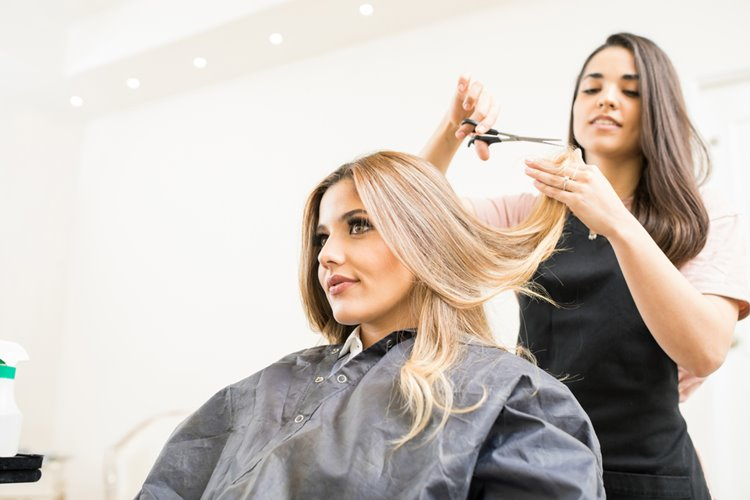 woman hairdresser giving haircut to client