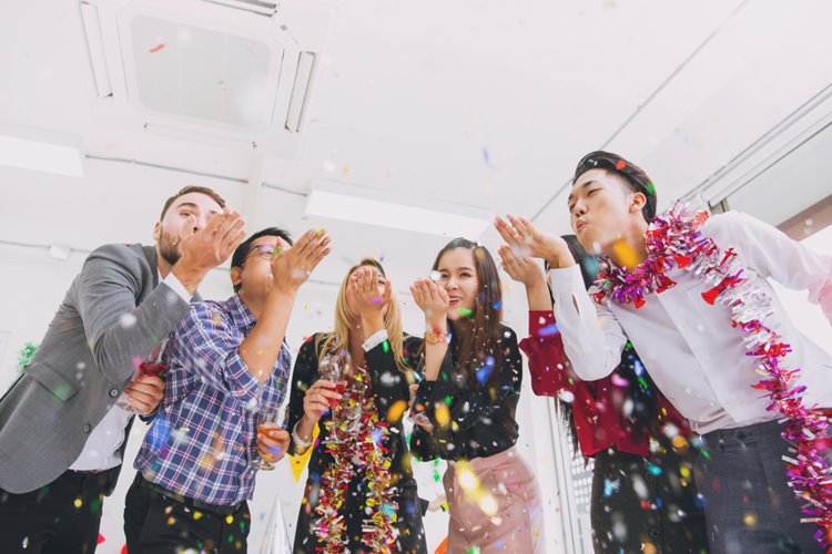 colleagues blowing confetti