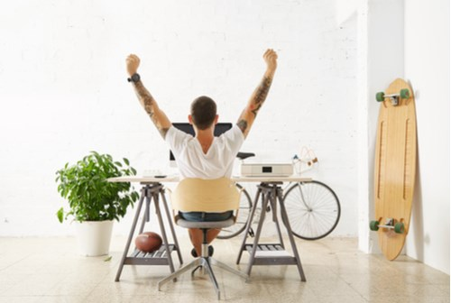 man with tattoos facing laptop and lifting arms in victory