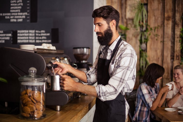 bearded man barista making coffee via coffee machine