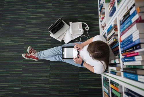 student sitting on library floor with tablet and laptop
