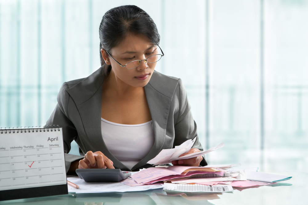 asian woman accountant with glasses calculating taxes