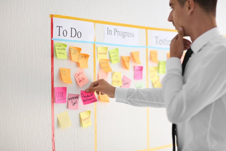 man allocating tasks that need to get done using post it notes