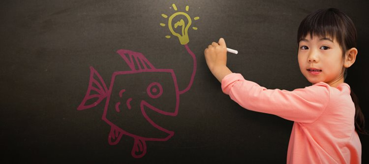 little asian girl drawing on fish and lighbulb on chalkboard