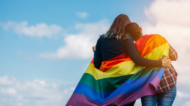 gay couple embracing each other with lgbt flag