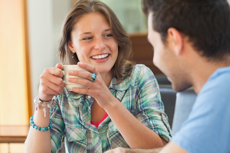 man and woman sharing stories over cup of coffee
