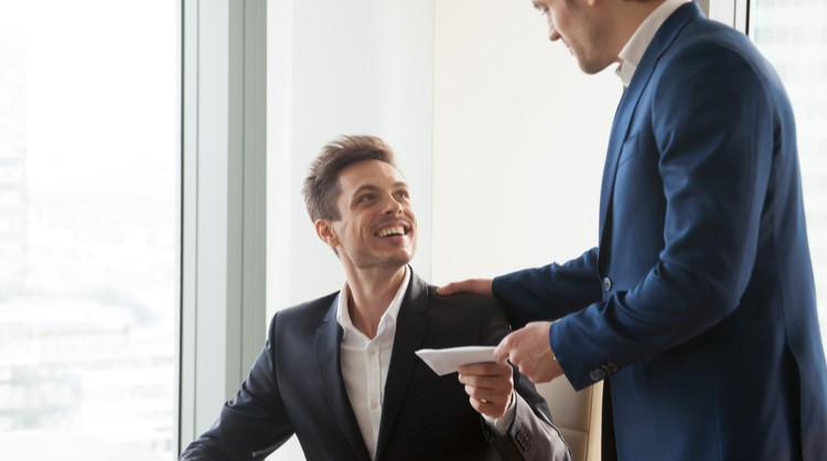 male boss giving envelope to male employee