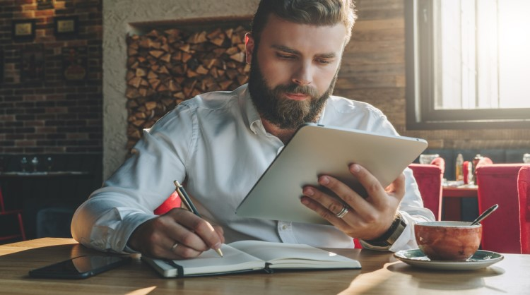 bearded young man reading on tablet