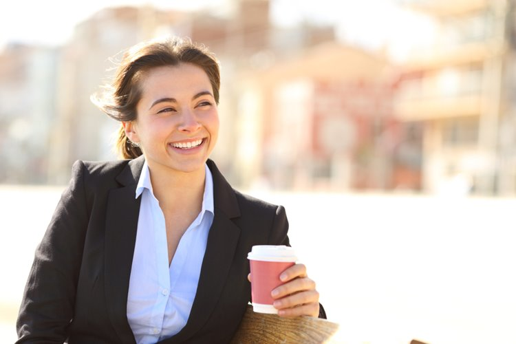 woman in business attire smiling with coffee in hand