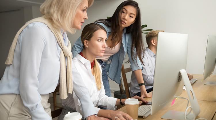 multiracial colleagues talking as a team around assistant's computer