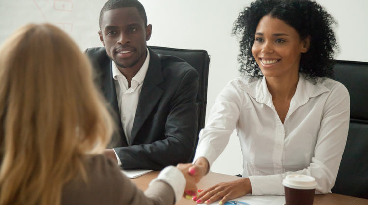 african american woman getting welcomed by HR team