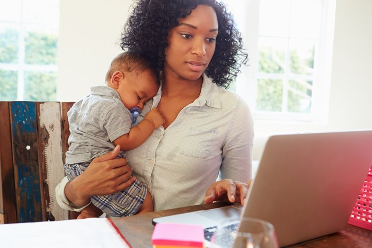 dark-skinned woman working on laptop with baby