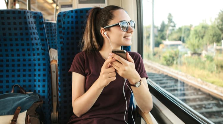 young woman smiling and listening to podcast