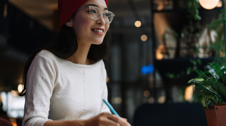 young asian woman with glasses smiling and working on something