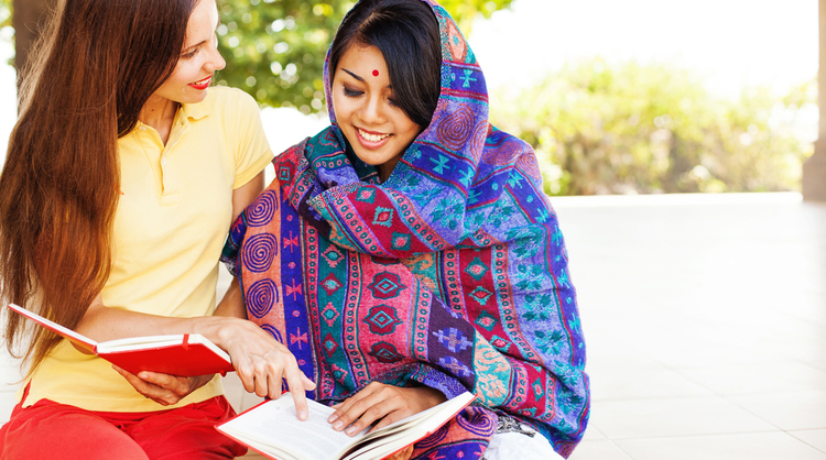 young woman teaching indian woman how to read in english