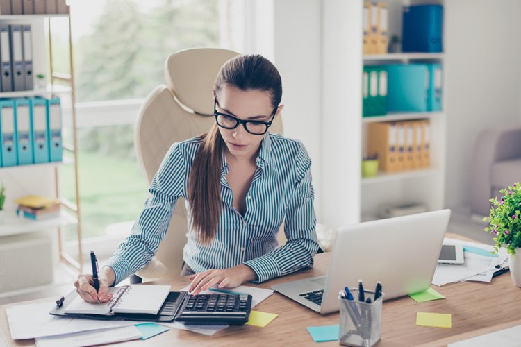 brunette haired woman with glasses working in home office