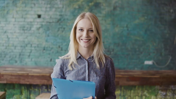 Blonde haired woman smiling with notebook