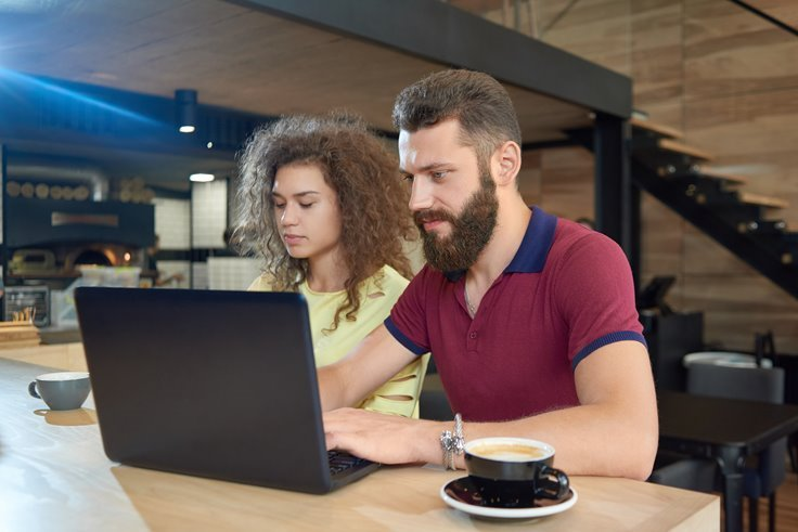 man and woman working together on laptop at cafe