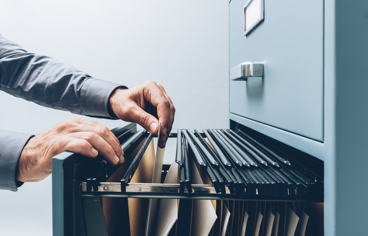 someone searching through filing cabinet