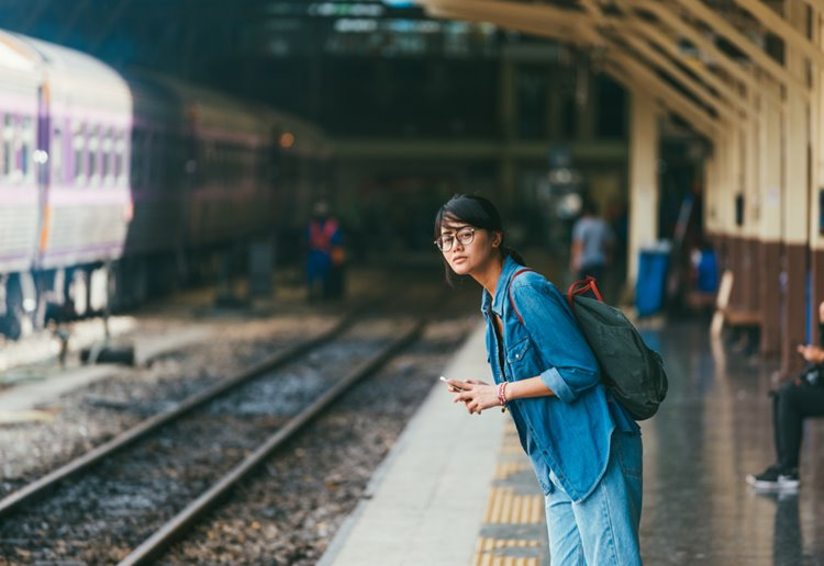 young asian woman with glasses waiting for train