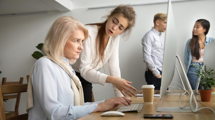 young team leader correcting older woman employee
