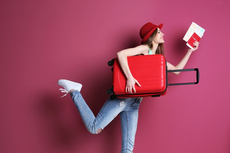 woman in coordinated outfit with red luggage bag