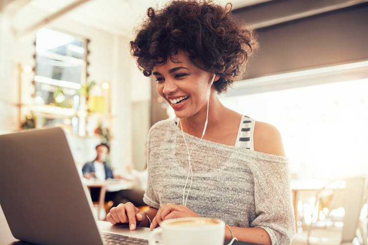 woman with curly haired woman smiling at laptop