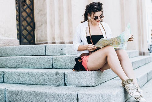 young woman with sunglasses sitting on step and looking at map