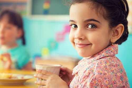 little girl smiling with cup in hand