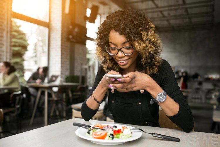 dark-skinned woman with curly hair taking photo of meal at restaurant